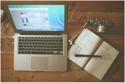 Picture of laptop, notebook, and pen on desk